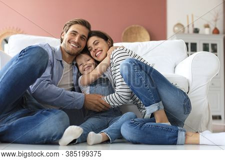 Young Caucasian Family With Small Daughter Pose Relax On Floor In Living Room, Smiling Little Girl K