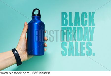 Black Friday Sales Text Near Female Hand Holding Aluminum Thermo Water Bottle Of Blue. Background Of
