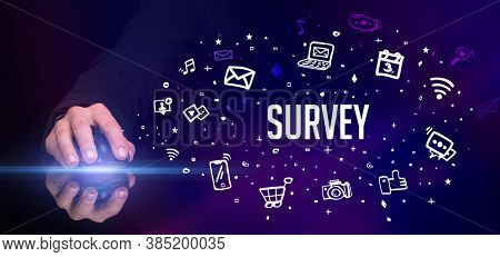 hand holding wireless peripheral with SURVEY inscription, social media concept