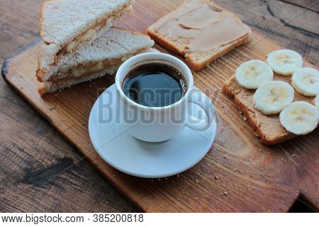 Cup Of Coffee And Peanut Butter Banana Toasts On Wooden Background. Slices Of Whole Wheat Bran Bread