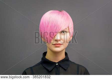 Portrait Of A Beautiful Young Caucasian Woman With Short Bright Pink Hair. Professional Hair Colorin