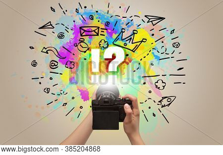 Close-up of a hand holding digital camera with abstract drawing and !? inscription