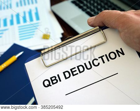 Qbi Qualified Business Income Deduction Documents In The Hand.