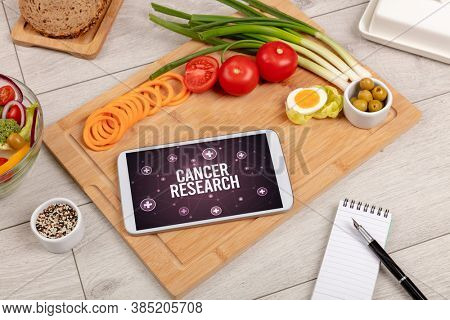 CANCER RESEARCH concept in tablet pc with healthy food around, top view