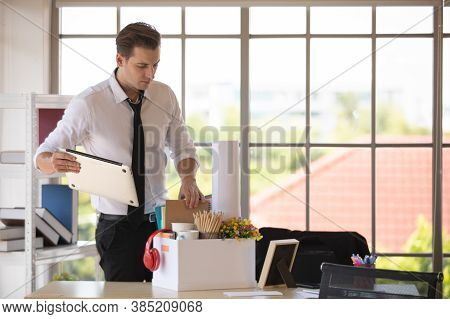 Young Caucasian Businessman Put Laptop Computer And Belongings Into Paper Box Prepare To Go Back Hom