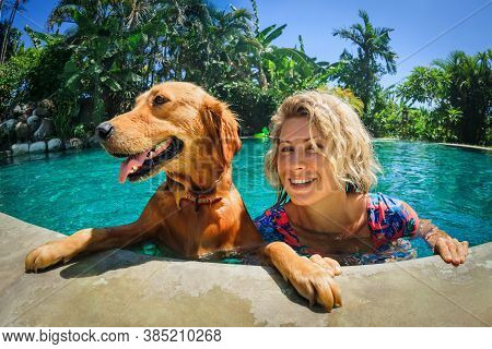 Funny Portrait Of Smiling Woman Relaxing With Golden Retriever Puppy In Tropical Swimming Pool. Popu