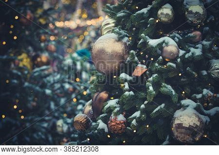 Evergreen Tree With Toys And Sparkling Garlands Covered With Snow Against The Background Of The Nigh
