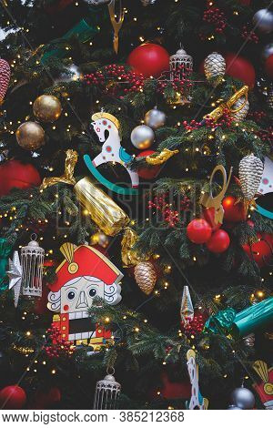 Evergreen Tree With A Variety Of Toys And Sparkling Garlands. Nutcracker Figurine And Other New Year
