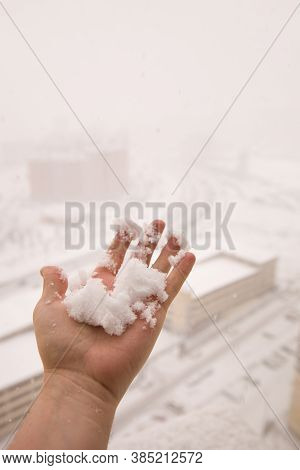 A Male Hand Holds A Freshly Fallen Snowball. View Of Real Snow With Selective Focus. Snow Falling Fr