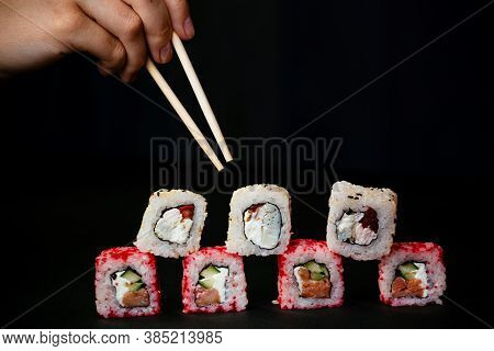 Female Hand Takes Chopsticks Sushi Rolls With Chinese Chopsticks. Lying On A Black Wooden Board. Vie