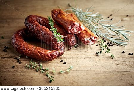 Rustic natural sausages with fresh herbs on rustic wooden background. Natural and organic food. Polish cuisine