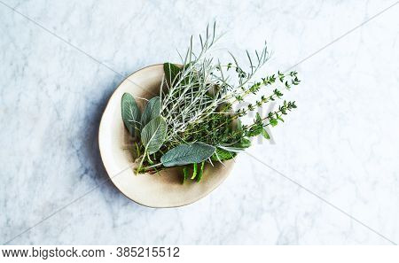Fresh organic herbs in a ceramic bowl. Natural food ingredients. Marble background