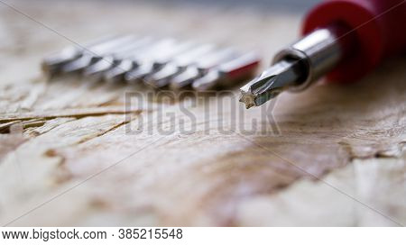 The Screwdriver Lies On A Wooden Background. Screwdriver With Five Edges. A Set Of Small Screwdriver