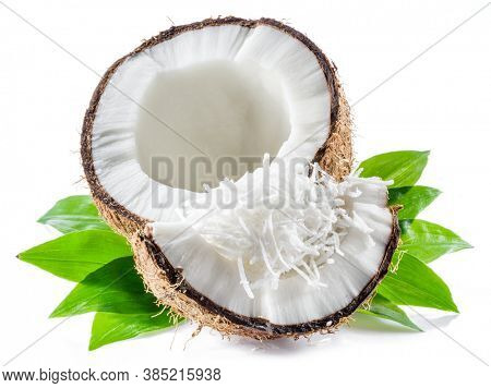 Cracked coconut fruit with white flesh and shredded coconut flakes isolated on white background.