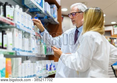 Two pharmacists, man and woman, searching for a product on a shelf