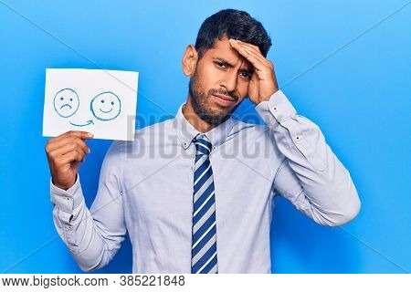 Young latin man holding sad to happy emotion paper stressed and frustrated with hand on head, surprised and angry face