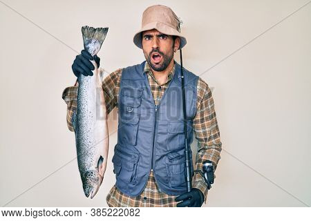 Handsome hispanic man with beard holding fishing rod and raw salmon in shock face, looking skeptical and sarcastic, surprised with open mouth