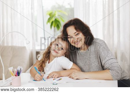Happy Mother And Her Smiling Daughter Draw On White Paper, Do Homework For School, Sit At Home Toget