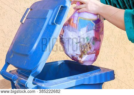 Woman Throws Garbage In A Blue Trash Can