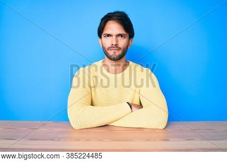 Handsome hispanic man wearing casual sweater sitting on the table skeptic and nervous, disapproving expression on face with crossed arms. negative person.