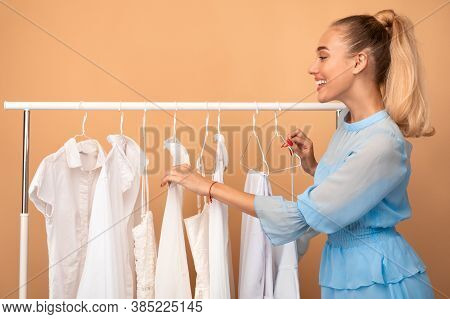 New Collection. Cheerful Young Woman Shopping In Fashion Mall, Choosing New Clothes, Customer Lookin