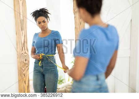 Unhappy Black Woman Measuring Waist With Tape Gaining Excess Weight Standing At Mirror Indoors. Sele