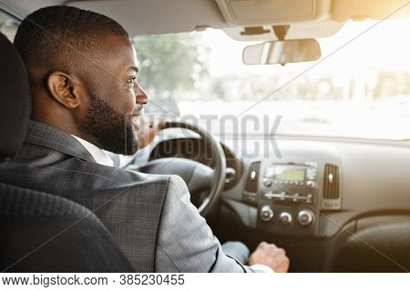 Closeup Of Smiling African American Businessman In Silver Suit Driving Car, Shot From Behind. Happy