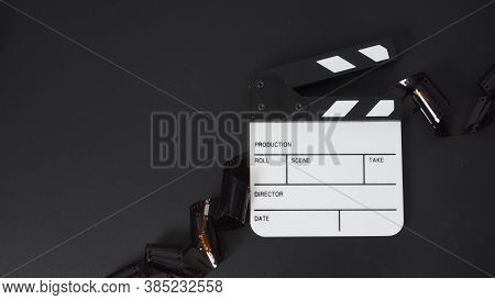 Small White Clapper Board And Film Roll On Black Background. It Use In Movie And Video Production In