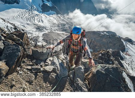 Climber In A Safety Helmet, Harness With Backpack Ascending A Rock Wall With Bionnassay Glacier On B