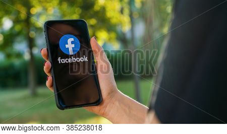 Berlin, Germany August 2019: Woman Hand Holding Iphone Xs With Logo Of Facebook Application In The P