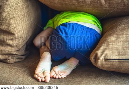 Rear View, Back Butt Legs Feet Of A Child Hiding Under A Pillow, Offended Boy In Bad Mood Or Playing