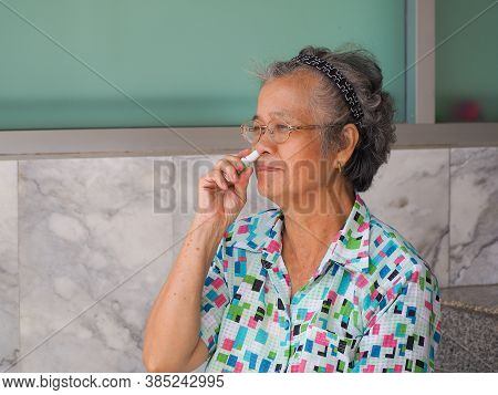 Asian Elderly Woman Using Herbal Inhaler While Sitting On Chair