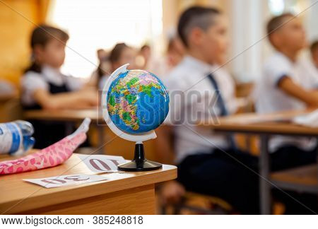 Teacher Giving Geography Lesson To Primary School Children In Classroom. Group Of Small School Kids