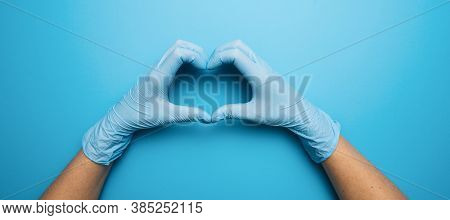 Doctor's Hands In Medical Gloves In Shape Of Heart On Blue Background, With Copyspace For Your Indiv