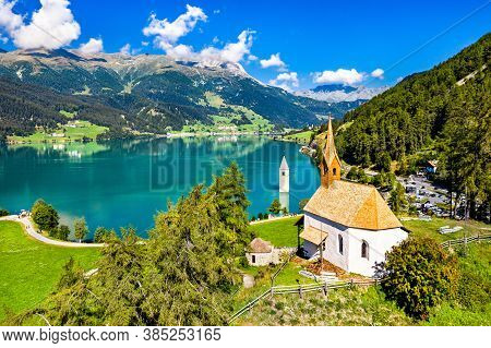St. Anna Chapel And Submerged Bell Tower Of Curon At Graun Im Vinschgau On Lake Reschen In South Tyr