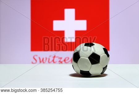 Small Football On The White Floor And Swiss Nation Flag With The Text Of Switzerland Background. The