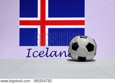 Small Football On The White Floor And Icelandic Nation Flag With The Text Of Iceland Background. The