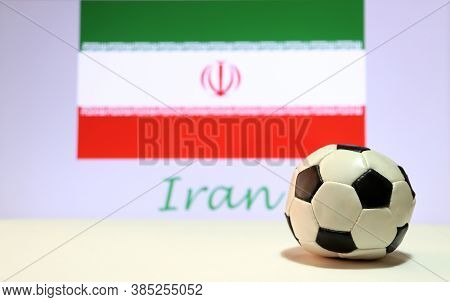 Small Football On The White Floor And Iranian Nation Flag With The Text Of Iran Background. The Conc
