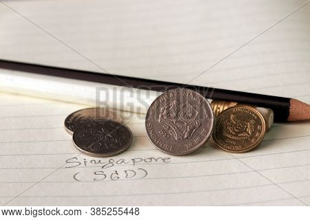 Singapore Cents Coin On Obverse (sgd) With Black And White Pencil On The Book.