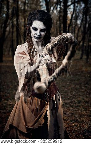 Halloween Theme: Mad Grim Voodoo Witch Killing By Staff. Portrait Of The Evil Hex In Dark Grove. Zom