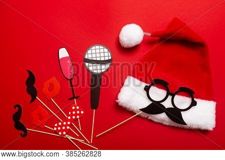A Red Color Banner With A Santa Hat With A White Pompom And A Face From Glasses And Mustache. A Prop