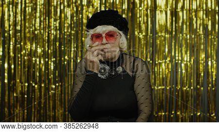 Elderly Style Granny Caucasian Mature Woman In Sunglasses Posing, Smoke Electronic Cigarette On Gold
