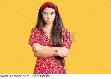 Brunette teenager girl wearing summer dress skeptic and nervous, disapproving expression on face with crossed arms. negative person.