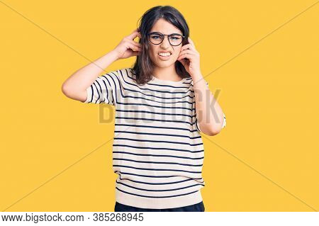 Brunette teenager girl wearing casual clothes and glasses covering ears with fingers with annoyed expression for the noise of loud music. deaf concept.