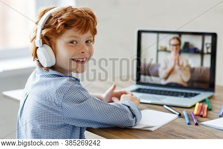 Happy Boy In Headphones Smiling And Looking At Camera While Making Video Call To Teacher During Onli