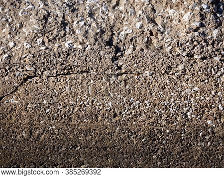 Interspersed Pebbles, Cracks And Dents Are Visible On The Surface Of The Old Cemented Wall. The Wall