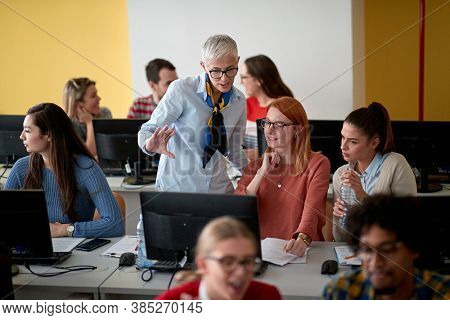 Female professor inspecting the work of students at an informatics lecture in the university computer class room