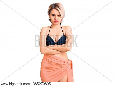 Young beautiful blonde woman wearing bikini skeptic and nervous, disapproving expression on face with crossed arms. negative person.
