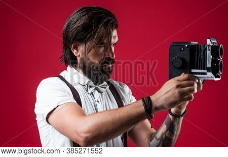 Handsome Photographer Guy In Suspenders Holding Vintage Camera While Standing Against Red Background
