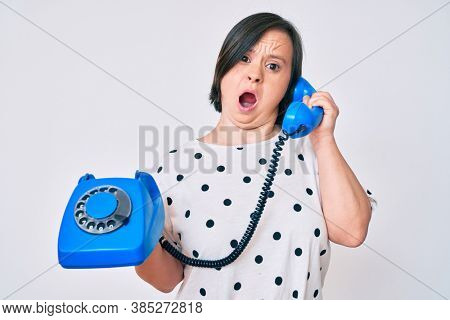 Brunette woman with down syndrome holding vintage telephone in shock face, looking skeptical and sarcastic, surprised with open mouth